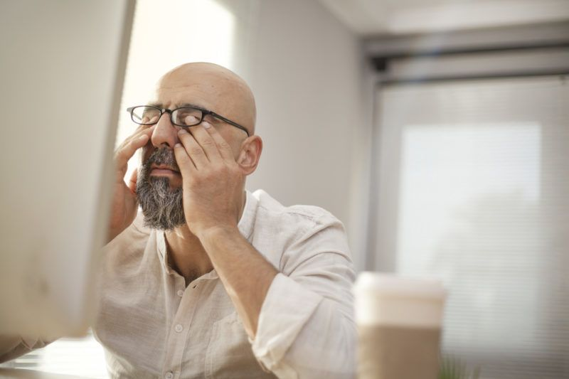 Senior businessman rubbing his tired eyes