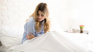 Young Caucasian woman in pajamas grabbing her belly while suffering from stomachache in her bed