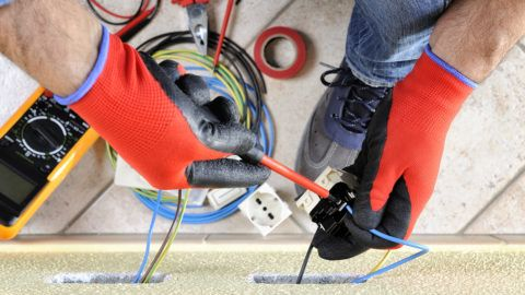 Electrician technician at work blocks the cable between the clamps of a socket in a residential electrical installation