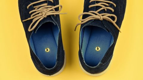 Abstract men's shoes with paper pins on yellow. Pranks and tricks concept for April fool's day