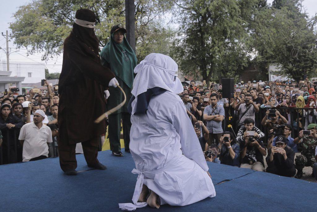 Banda Aceh, 2018. április 20. Prostitúcióval vádolt nõt botoznak nyilvánosan az indonéziai Aceh tartomány székhelyén, Banda Acehben 2018. április 20-án. Az iszlám vallási törvénykezés, a saría ellen vétõk botozása nagy valószínûséggel az utolsó ilyen nyilvános esemény, ugyanis a tartomány kormányzója a hónap elején jelentette be, hogy az ilyen jellegû büntetéseket zárt ajtók mögött hajtják majd végre. A botozás a mélyen konzervatív Aceh tartományban alkalmazott saría egyik büntetési formája. (MTI/AP/Heri Juanda)