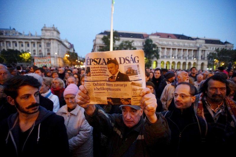 """Budapest, 2016. október 8.Egy férfi az utolsó lapszámot mutatja a Népszabadság melletti szimpátiatüntetésen a Kossuth téren, a Parlamentnél 2016. október 8-án. A Mediaworks kiadó ezen a napon bejelentette, hogy felfüggeszti a Népszabadság nyomtatott és internetes formában történő kiadását a lap új koncepciójának kialakításáig, illetve megvalósításáig azért, hogy """"valamennyi érintett ezen kiemelt feladatra tudjon koncentrálni"""". A kiadó tájékoztatása szerint a lap eddig 5 milliárd forintos veszteséget termelt.MTI Fotó: Balogh Zoltán"""