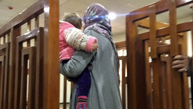 A picture taken on February 19, 2018, shows French Jihadist Melina Bougedir carriyng hers soon arriving in court in the Iraqi capital Baghdad. Melina Bougedir, 27, was arrested last summer in former Islamic State group stronghold Mosul with her four children, three of whom have been repatriated to France. / AFP PHOTO / STRINGER