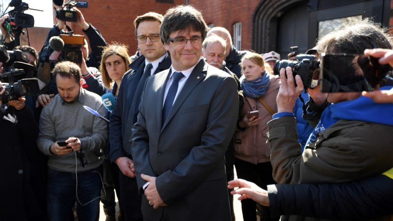 Catalonia's ousted leader Carles Puigdemont poses for photographers as he leaves the detention centre (Justizvollzugsanstalt, JVA) of Neumuenster, northern Germany, on April 6, 2108 after judges refused his extradition to Spain on a rebellion charge and ordered him freed on bail pending a ruling on a lesser corruption charge.  A German court on April 5, 2018 refused a request from Spain to extradite Puigdemont on a rebellion charge following his arrest in Germany last month, and ordered his release on bail pending a hearing on a lesser charge. / AFP PHOTO / Patrik STOLLARZ