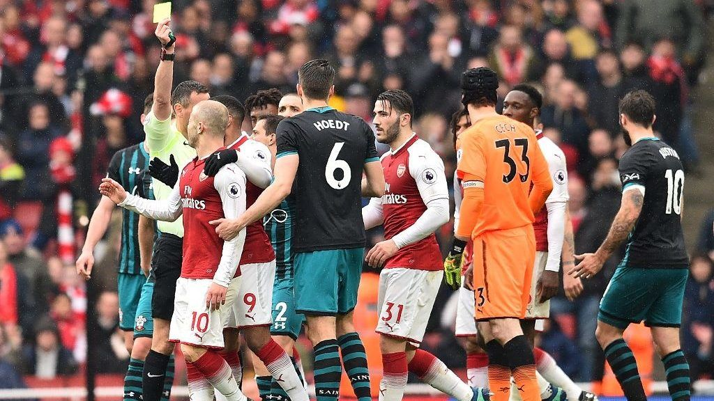 Referee Andre Marriner gives Arsenal's English midfielder Jack Wilshere a yellow card during the English Premier League football match between Arsenal and Southampton at the Emirates Stadium in London on April 8, 2018.  / AFP PHOTO / Glyn KIRK / RESTRICTED TO EDITORIAL USE. No use with unauthorized audio, video, data, fixture lists, club/league logos or 'live' services. Online in-match use limited to 75 images, no video emulation. No use in betting, games or single club/league/player publications.  /