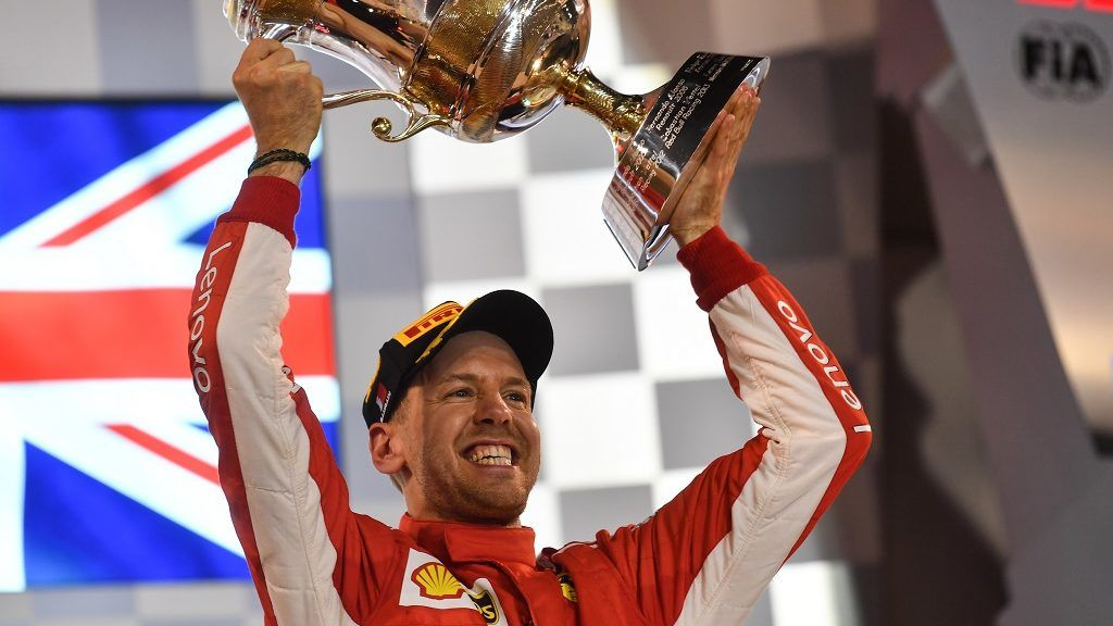 Ferrari's German driver Sebastian Vettel raises his trophy on the podium after winning the Bahrain Formula One Grand Prix at the Sakhir circuit in Manama on April 8, 2018.  / AFP PHOTO / Andrej ISAKOVIC