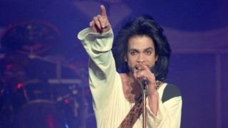 (FILES) In this file photo taken on June 16, 1990 shows musician Prince performing on stage during his concert at the Parc des Princes stadium in Paris.   A Minnesota prosecutor on April 19, 2018 declined to file criminal charges over pop icon Prince's death from a painkiller overdose, saying a two-year investigation did not find evidence of intentional wrongdoing.Federal authorities, however, announced a settlement with a doctor who gave the powerful drugs to Prince that will include monitoring of his future prescriptions.  / AFP PHOTO / Bertrand GUAY