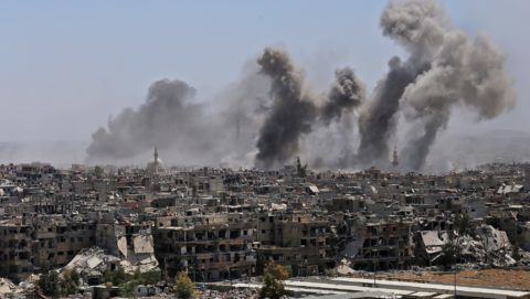 A picture taken during a government guided tour shows smoke rising from buildings in Yarmuk, a Palestinian refugee camp on the edge of Damascus, during regime shelling targeting Islamic State (IS) group positions in the  southern district of the capital on April 24, 2018.  In 2015, IS overran most of Yarmuk, and the small numbers of other rebels and jihadists, including from Al-Qaeda's former affiliate, that had a presence there agreed to withdraw just a few weeks ago. / AFP PHOTO / Maher AL MOUNES
