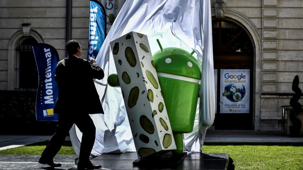A man unveils a statue donated by Google on September 21, 2016 in Montelimar, as Google decided to launch a new version of the android operating system called Android 7.0 or Nougat.  / AFP PHOTO / JEFF PACHOUD