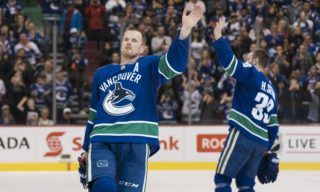 VANCOUVER, BC - OCTOBER 5: Daniel Sedin #22 and Henrik Sedin #33 of the Vancouver Canucks waves to the fans after playing in their final home game of their career against the Arizona Coyotes in NHL action on April, 5, 2018 at Rogers Arena in Vancouver, British Columbia, Canada.   Rich Lam/Getty Images/AFP