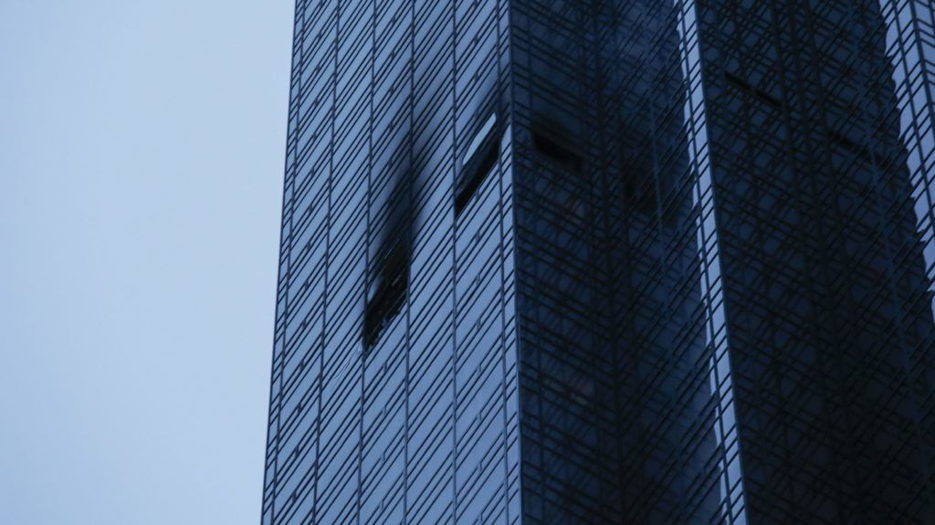NEW YORK, NY - APRIL 07: Broken and burned windows are seen after a fire broke out on the 50th floor of Trump Tower on April 7, 2018 in New York City. One person has reportedly died and four firefighters were injured in the four-alarm blaze.   Eduardo Munoz Alvarez/Getty Images/AFP