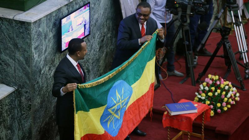 ADDIS ABABA, ETHIOPIA - APRIL 2:  Abiy Ahmed (L), newly elected Prime Minister of Ethiopia, holds an Ethiopian flag with his predecessor, Hailemariam Dessalegn,  at the House of Peoples' Representatives following the swearing in ceremony on April 2, 2018 in Addis Ababa. Minasse Wondimu Hailu / Anadolu Agency