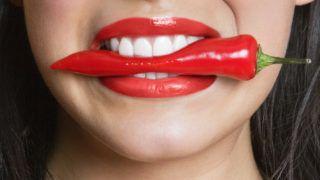 Close-up portrait of Hispanic woman biting red pepper