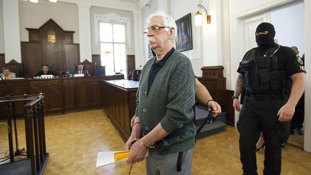 Szombathely, 2018. április 25.Tárgyalóterembe vezetik a bőnyi rendőrgyilkossággal vádolt Győrkös Istvánt a büntetőper tárgyalásának első napján a Szombathelyi Törvényszéken 2018. április 25-én. A vádirat szerint Győrkös István bőnyi lakásán a Készenléti Rendőrség hatósági engedély nélkül tartott lőfegyverek gyanúja miatt tartott házkutatást 2016. október 26-án. A vádlott három lövésből álló sorozatot adott le egy 46 éves rendőrre, az egyik lövedék az áldozat fejét érte, aki ebbe a sérülésbe belehalt.MTI Fotó: Varga György