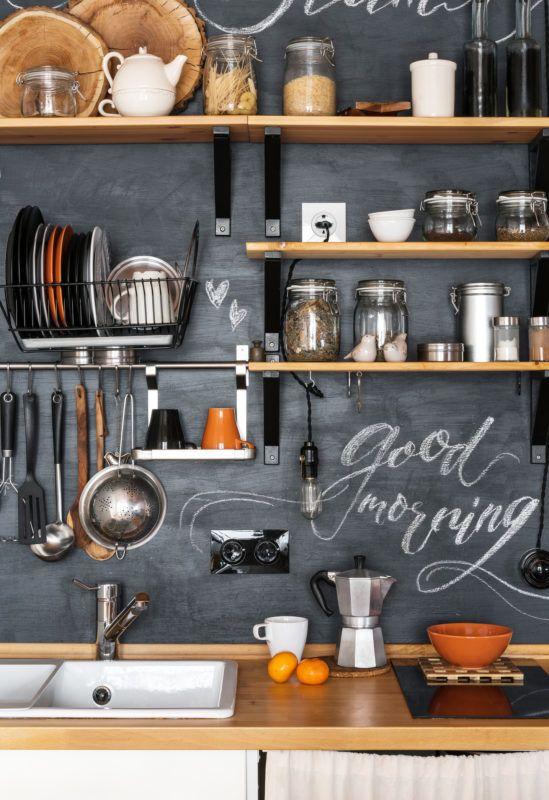 """Design of modern kitchen in loft and rustic style. Wooden Shelves with different jars on a black wall with chalk """"Good Morning"""""""