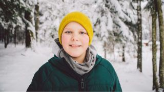 A young boy poses for a portrait amidst forest deep in snow. Lithuania, January 2018.