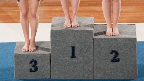 Winning Smiles From Teenaged Gymnasts Standing On Winner Podium Wearing Medal