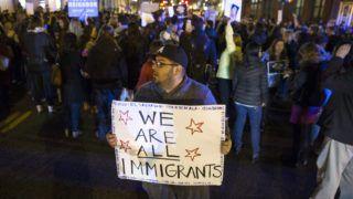 """Washington, 2017. január 26. """"Mindannyian bevándorlók vagyunk"""" feliratú transzparenssel tiltakozik egy résztvevõ a Donald Trump amerikai elnök elleni tüntetésen a washingtoni Fehér Ház közelében 2017. január 25-én. (MTI/EPA/Shawn Thew)"""