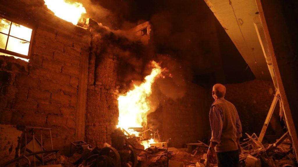 Dúma, 2018. március 23. Légicsapástól lángba borult épületet néz egy szíriai férfi a Dzsejs al-Iszlám felkelõcsoport ellenõrzése alatt álló kelet-gútai Dúmában 2018. március 23-ra virradóra. Az éjjel életbe lépett tûzszüneti megállapodás ellenére folytatódnak a kormányerõk és a lázadók közti harcok a Damaszkusz melletti Kelet-Gúta több településén. (MTI/EPA/Mohamed Badra)
