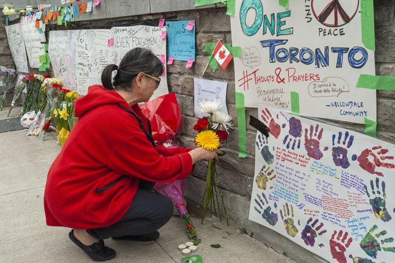 Toronto, 2018. április 24.Virágot hagy egy nő a torontói tömeges gázolás áldozatainak rögtönzött emlékhelyén 2018. április 24-én. Az előző napon egy férfi bérelt kisteherautóval járókelők közé hajtva 25 embert elgázolt, akik közül tíz meghalt. A 25 éves gyanúsítottat, Alek Minassiant elfogták, és vádat emeltek ellene. (MTI/EPA/Warren Toda)