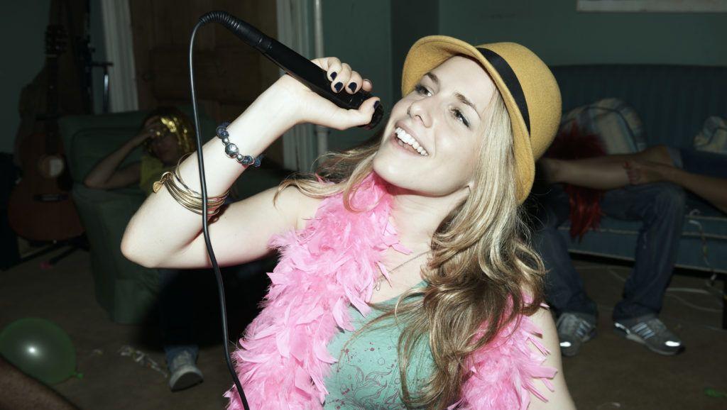 Woman singing karaoke at house party