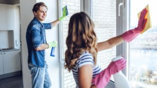 Young happy couple is washing windows while doing cleaning at home.