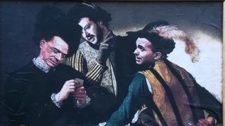 """A painting made by street artist Sirante showing Forza Italia (Go Italy) leader Silvio Berlusconi (L), Lega leader Matteo Salvini (C) and Five Star Mouvement ( M5S ) leader Luigi Di Maio featured as in the original Caravaggio painting """"I Bari"""" ( The cardsharps ) is seen in down town Rome on April 13, 2018.Far-right and anti-establishment forces in Italy resumed battle on Thursday over who can lead a new government, as a second round of talks began with a row over Silvio Berlusconi leaving little room for manoeuvre after last month's inconclusive election. / AFP PHOTO / Fanny CARRIER / RESTRICTED TO EDITORIAL USE - MANDATORY CREDIT NAME OF THE ARTIST - NO MARKETING NO ADVERTISING CAMPAIGNS"""