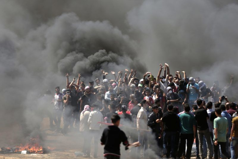 """Palestinian demonstrators burn tyres near the Gaza-Israel border, east of Gaza City, as Palestinians readied for protests over the inauguration of the US embassy following its controversial move to Jerusalem on May 14, 0218.  / AFP PHOTO / MAHMUD HAMS / """"The erroneous mention[s] appearing in the metadata of this photo by MAHMUD HAMS has been modified in AFP systems in the following manner: [May] instead of [July]. Please immediately remove the erroneous mention[s] from all your online services and delete it (them) from your servers. If you have been authorized by AFP to distribute it (them) to third parties, please ensure that the same actions are carried out by them. Failure to promptly comply with these instructions will entail liability on your part for any continued or post notification usage. Therefore we thank you very much for all your attention and prompt action. We are sorry for the inconvenience this notification may cause and remain at your disposal for any further information you may require."""""""