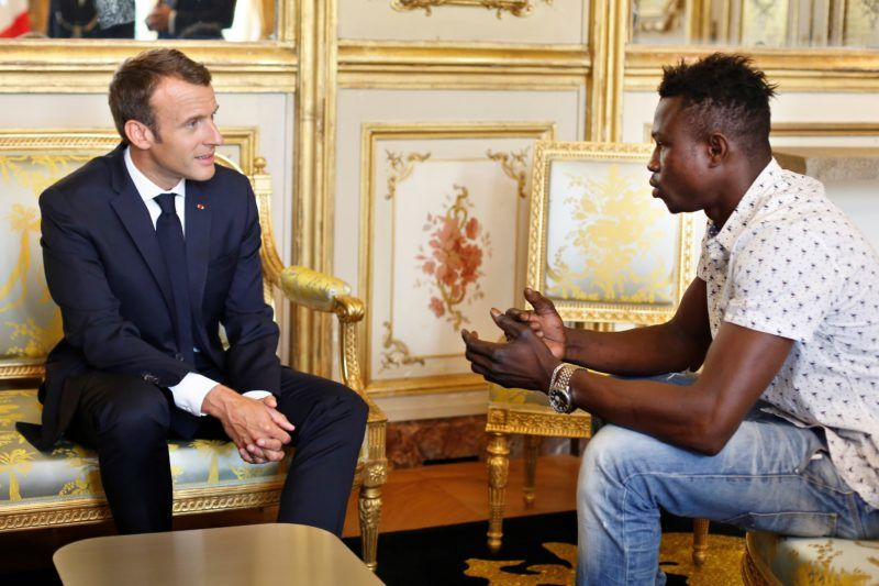 French President Emmanuel Macron (L) speaks with Mamoudou Gassama, 22, from Mali, at the presidential Elysee Palace in Paris, on May, 28, 2018.  Mamoudou Gassama living illegally in France is being honored by Macron for scaling an apartment building over the weekend to save a 4-year-old child dangling from a fifth-floor balcony. / AFP PHOTO / POOL / Thibault Camus