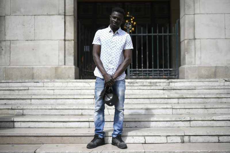 A 22-year old Mamoudou Gassama from Mali poses in front of the townhall of Montreuil, eastern Paris suburb, on May 28, 2018. Mamoudou Gassama living illegally in France is being honored by French President for scaling an apartment building on May 26 to save a 4-year-old child dangling from a fourth-floor balcony.  / AFP PHOTO / Lionel BONAVENTURE