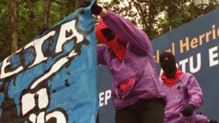 plusieurs militants indépendantistes basques, en cagoules, déroulent des affiches, le 12 aoűt 2000 ŕ Bilbao, lors de la mobilisation de milliers de personnes, pour rendre hommage aux quatre militants de l'ETA tués le 9 aoűt dernier, par une bombe qu'ils transportaient.Hooded supporters of Basque nationalismunf url their banners 12 August in Bilbao, as thousands turned out to honour four members of the Basque seperatist group ETA blown up by a bomb they were transporting / AFP PHOTO / DANIEL VELEZ
