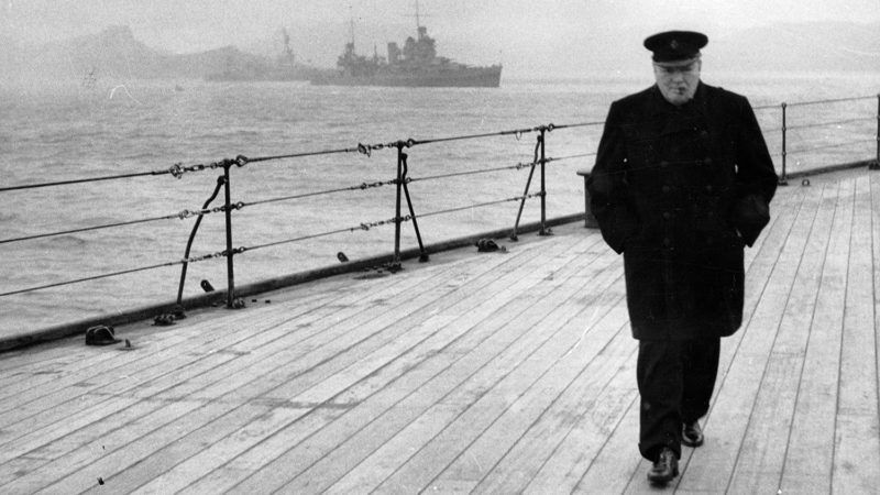 """World War II (Second World War) : Winston Spencer Churchill (1874-1965) British statesman, in overcoat and hat and smoking a cigar, walking alone on the deck of HMS """"Prince of Wales"""" during the Atlantic Conference in 1941.World History Archive"""