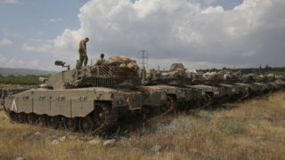 """Israeli Merkava Mark IV tanks take position near the Syrian border in the Israeli-annexed Golan Heights on May 9, 2018.  The Israeli-occupied section of the Golan Heights was placed on high alert due to """"irregular activity by Iranian forces"""" across the demarcation line in Syria. / AFP PHOTO / JALAA MAREY"""