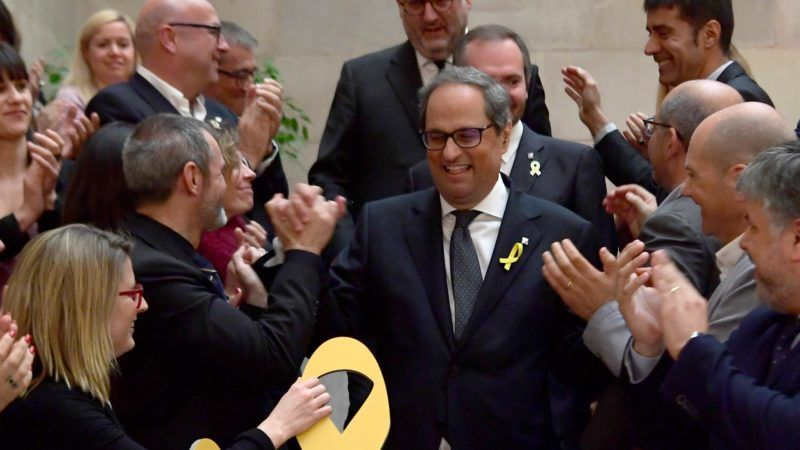 New elected Catalan regional president Quim Torra (C) is congratulated by members of his Junts per Catalonia (Together for Catalonia) parliamentary group after a vote session at the Catalan parliament in Barcelona on May 14, 2018. Quim Torra, a newcomer to politics who has long fiercely campaigned for independence in Catalonia, was appointed regional president today, vowing to keep fighting for an independent republic.       / AFP PHOTO / LLUIS GENE