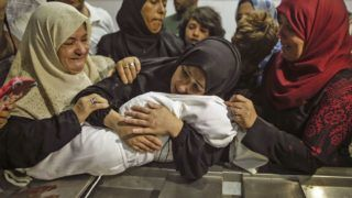 The mother of a Leila al-Ghandour (C), a Palestinian baby of 8 months who according to Gaza's health ministry died of tear gas inhalation during clashes in East Gaza the previous day, holds her at the morgue of al-Shifa hospital in Gaza City on May 15, 2018 Fresh protests are expected a day after Israeli forces killed 59 Palestinians during clashes and protests along the Gaza border against the US embassy opening in Jerusalem in the conflict's bloodiest day in years. / AFP PHOTO / MAHMUD HAMS