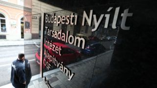 """A man walks past the entrance of the building that houses the Open Society Foundations run by US-Hungarian billionaire George Soros, on May 15, 2018 in Budapest.  The foundation announced on  May 15, 2018 it was closing its operations in Hungary and relocating to Berlin, Germany, in response to the """"repressive"""" policies of Viktor Orban's government.   / AFP PHOTO / FERENC ISZA"""
