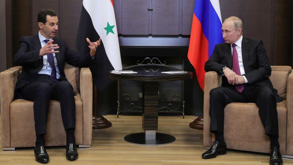 Russian President Vladimir Putin (R) speaks with his Syrian counterpart Bashar al-Assad during their meeting in Sochi on May 17, 2018. / AFP PHOTO / SPUTNIK / Mikhail KLIMENTYEV