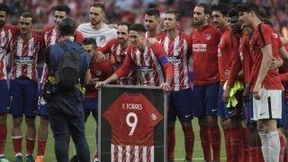 Atletico Madrid's Spanish forward Fernando Torres poses with teammates and a signed framed jersey at the end of the Spanish league football match between Club Atletico de Madrid and SD Eibar at the Wanda Metropolitano stadium in Madrid on May 20, 2018. Torres scored twice in what was his final match for Atletico Madrid. / AFP PHOTO / GABRIEL BOUYS