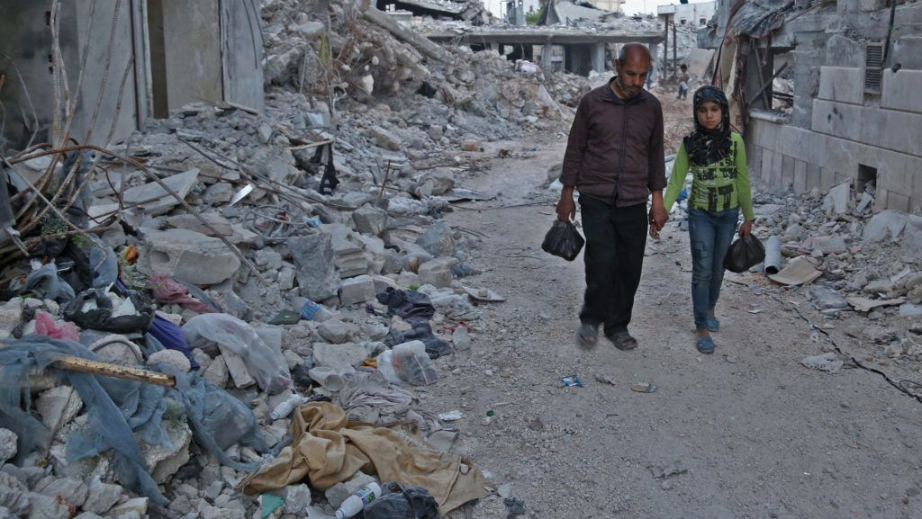 Syrian girl Inas, daughter of Mehdi Haymur (L), walks in Afrin, on May 26, 2018. Displaced from their homes in Syria's Eastern Ghouta, families sought refuge in abandoned houses in the traditionally Kurdish town of Afrin. Afrin itself had been emptied of its residents just weeks earlier, after a brutal Turkish-led offensive forced tens of thousands to flee. / AFP PHOTO / Nazeer AL-KHATIB