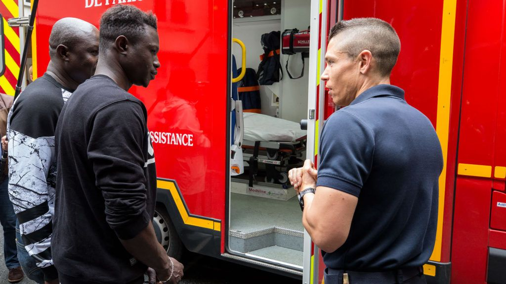 """This handout picture taken and released by the Paris Fire Brigade (Brigade des sapeurs-pompiers de Paris - BSPP) on May 29, 2018, shows Mamoudou Gassama (2nd L), the 22-year-old Malian """"Spiderman"""" feted for saving a child hanging from a balcony, visiting the Paris Fire Brigade headquarters and Champerret fire station in Paris. Gassama took his first step toward French citizenship May 29 and joined the fire brigade as accolades continued to pour in over his daring rescue. Video footage of Gassama scaling four storeys of the building with his bare hands has catapulted the young man to global fame, and earned him the promise of citizenship from President Emmanuel Macron.  / AFP PHOTO / BSPP - Brigade de sapeurs-pompiers de Paris / Erwan Thepault / RESTRICTED TO EDITORIAL USE - MANDATORY CREDIT """"AFP PHOTO / BSPP / ERWAN THEPAULT"""" - NO MARKETING NO ADVERTISING CAMPAIGNS - DISTRIBUTED AS A SERVICE TO CLIENTS"""