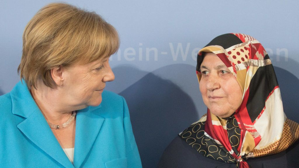 29 May 2018, Germany, Duesseldorf: The German Chancellor Angela Merkel of the Christian Democratic Union (CDU) standing beside Mevlude Genc (R), mother, grandmother, and aunt of victims. 25 years after the racially motivated arson attack of Solingen, the victims are honoured with two events. In the night of 29 May 1993, four right-wing extremists set fire to the house of the Turkish family Genc in North Rhine-Westphalia. Five women and girls lost their lives. Photo: Rolf Vennenbernd/dpa