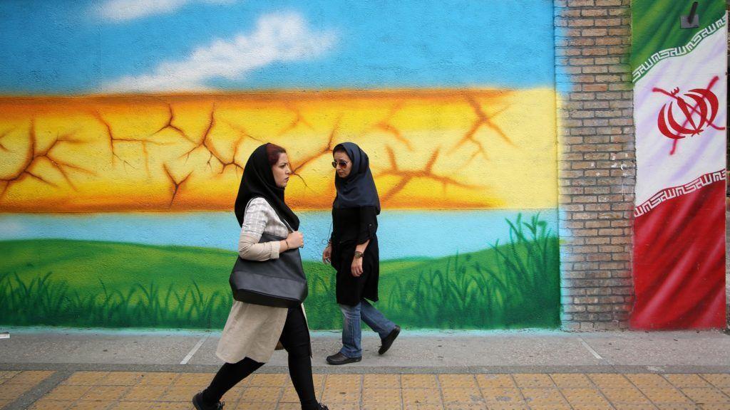 TEHRAN, IRAN - MAY 08: Women walk past mural paintings on the walls in Tehran, Iran on May 08, 2018.  Fatemeh Bahrami / Anadolu Agency