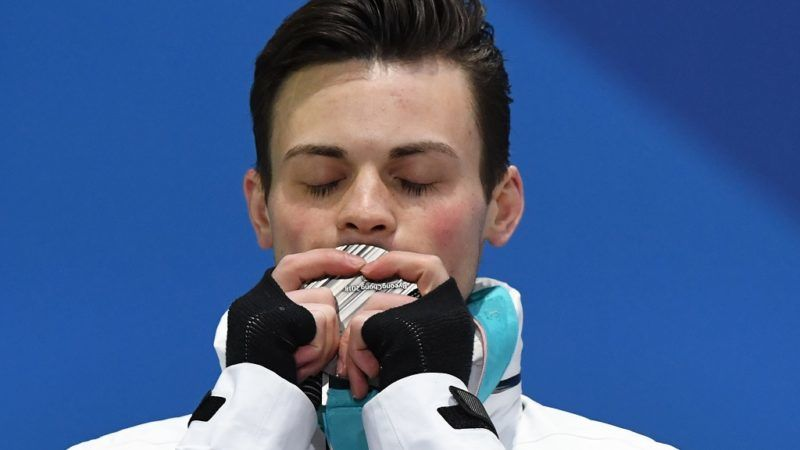 USA's silver medallist John-Henry Krueger kisses his medal on the podium during the medal ceremony for the short track men's 1000m at the Pyeongchang Medals Plaza during the Pyeongchang 2018 Winter Olympic Games in Pyeongchang on February 18, 2018. / AFP PHOTO / JAVIER SORIANO