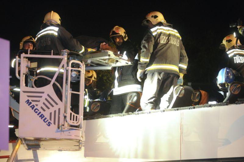 Budapest, 2018. május 29. Tûzoltók emelik le a baleset egyik sérüljét egy összeroncsolódott emeletes autóbuszról a Ferihegyi repülõtérre vezetõ úton 2018. május 29-re virradó éjjel, miután a külföldi rendszámú jármû a Felsõcsatári úti aluljáró elõtti magasságkorlátozó kapunak rohant. Az elsõdleges információk szerint a balesetben többen megsérültek. A munkálatok idejére a gyorsforgalmi út érintett szakaszát teljes szélességében lezárták. MTI Fotó: Mihádák Zoltán