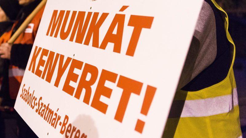 """Mátészalka, 2015. február 9. Az emberi méltóság menete elnevezésû demonstráció résztvevõi Mátészalkán, a járási hivatal épülete elõtt rendezett gyûlésen 2015. február 9-én. A Közmunkás Szakszervezet tüntetésének résztvevõi Gyõrtelekrõl Kocsordon át vonultak a szatmári városba. A demonstrálók """"a szegényeket sújtó politika megszüntetését, a vidék leszakadásának megállítását, a közmunkások helyzetének javítását, egy igazságos, szolidáris, szabad Magyarország létrehozását"""", valamint a minimálbér emelését és a közszféra dolgozóinak 5 százalékos béremelését követelték. MTI Fotó: Balázs Attila"""