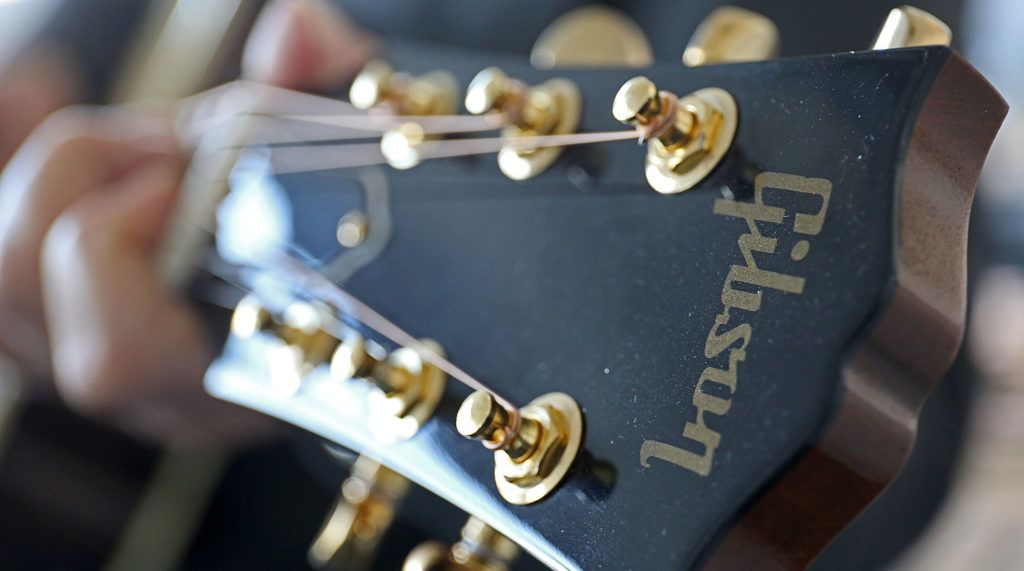 21 February 2018, Germany, Cologne: The logo reads 'Gibson' on the headstock of a Gibson acoustic guitar. The established guitar manufacturer from Nashville has to face an existential struggle: According to a 'Nashville Post' report, the guitar manufacturer is to have piled up debts in the amount of half a billion US dollars. Photo: Oliver Berg/dpa