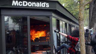 Párizs, 2018. május 1. Tüntetõk rugdossák egy általuk felgyújtott McDonald's étterem üvegeit Párizsban 2018. május 1-jén. (MTI/AP/Francois Mori)