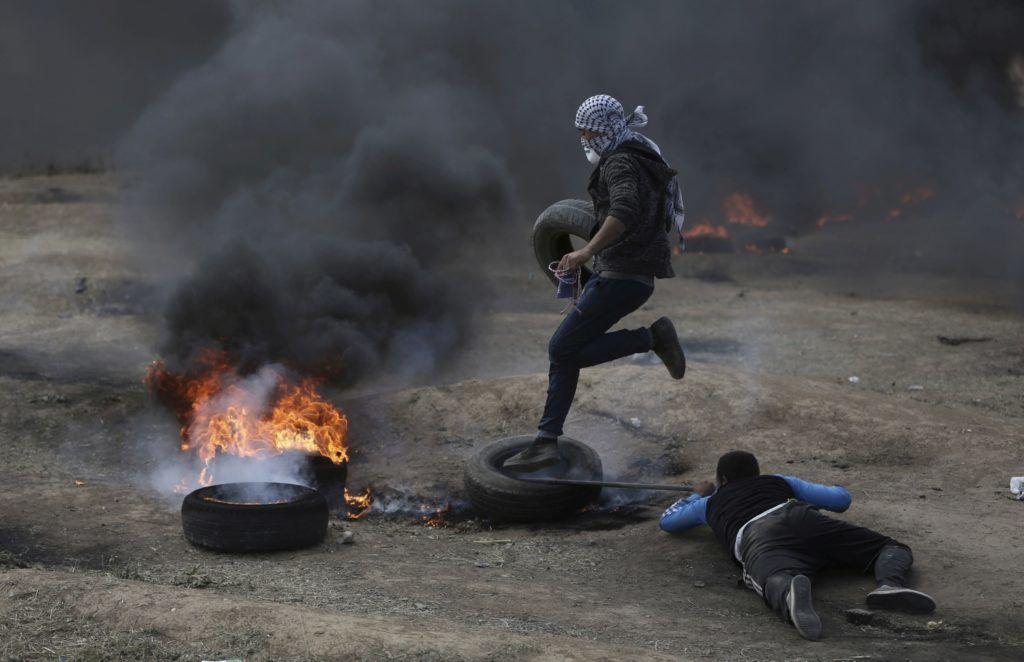 Gáza, 2018. május 14. Palesztin tüntetõ égõ gumiabroncsok füstjében a határon lévõ szögesdrótkerítés mellett, Gáza városától keletre 2018. május 14-én.Az izraeli katonák elleni harcban 93 palesztin sebesült meg, egy 21 éves tüntetõt agyonlõttek. Ezen a napon, Izrael Állam megalapításának 70. évfordulóján nyílik meg a Tel-Avivbõl Jeruzsálembe költöztetett amerikai nagykövetség, amivel az Egyesült Államok kifejezésre juttatja, hogy Jeruzsálemet ismeri el Izrael fõvárosaként. (MTI/Halil Hamra)
