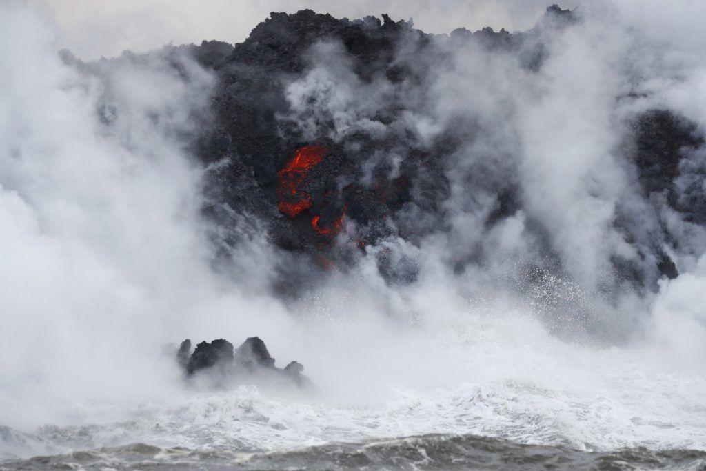 Pahoa, 2018. május 21. A Kilauea tûzhányó lávafolyama belemömlik a Csendes-óceánba a hawaii Nagy-szigeten fekvõ Pahoa város környékén 2018. május 21-én. A világ egyik legaktívabb tûzhányójának számító Kilauea vulkáni tevékenysége május 3. óta tart. A környékén kötelezõ kitelepítés van érvényben, a lávafolyam eddig 44 házat pusztított el. Jelenleg tilos az óceánban való fürdõzés a térségben, mert a láva és az óceánvíz találkozásakor veszélyes sósav keletkezhet, a vulkán pedig egyre nagyobb mértékben lövell ki szintén mérgezõ kén-dioxidot. (MTI/AP/Jae C. Hong)