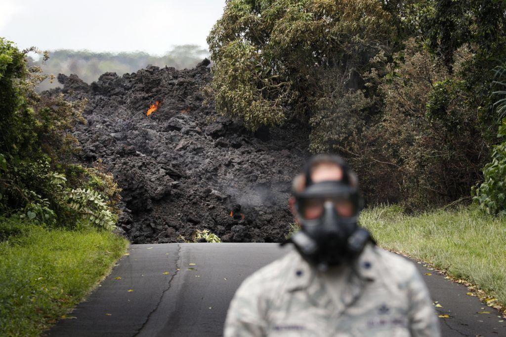 Pahoa, 2018. május 21. Az amerikai légierõ tisztje gázmaszkot visel a Kilauea tûzhányó lávaömlenye közelében egy autóúton, a hawaii Nagy-szigeten fekvõ Pahoa város környékén 2018. május 20-án. A világ egyik legaktívabb tûzhányójának számító Kilauea vulkáni tevékenysége május 3. óta tart. A környékén kötelezõ kitelepítés van érvényben, a lávafolyam eddig 44 házat pusztított el. Jelenleg tilos az óceánban való fürdõzés a térségben, mert a láva és az óceánvíz találkozásakor veszélyes sósav keletkezhet, a vulkán pedig egyre nagyobb mértékben lövell ki szintén mérgezõ kén-dioxidot. (MTI/AP/Jae C. Hong)